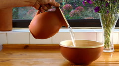 Man's hand pouring a jug of water into a bowl. Stock Footage