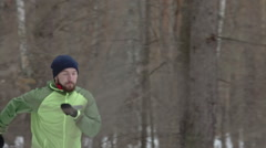 Young man practicing running in cold weather Stock Footage