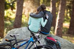 Biker couple sitting on rock in forest Stock Photos