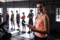 Happy female fitness instructor holding clipboard Stock Photos
