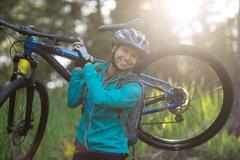 Portrait of female biker carrying mountain bike Stock Photos