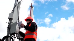 An engineer working with the antennas and transmitters on the tower, male Stock Footage
