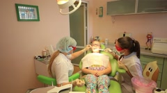 Dentists puts baby dental fillings with blue light Stock Footage