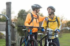 Biker couple interacting while standing with mountain bike Stock Photos