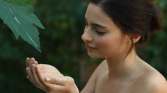A Beautiful young woman takes a drop of clear water from a leaf Stock Footage