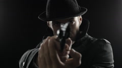Portrait of a gangster in a hat and a black cloak takes aim with a revolver Stock Footage