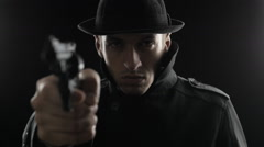 Portrait of a gangster in a hat and a black cloak threatens weapon Stock Footage