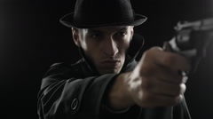Gangster in a hat and a black cloak. Mafioso aiming a gun at the camera Stock Footage