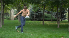 The guy is dancing hip-hop on green grass Stock Footage