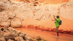 Tourist Makes Selfie against Red Hills of Fairy Stream Stock Footage