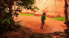 Tourist Walks to Sun Reflection on Fairy-Stream Red Waters Stock Footage