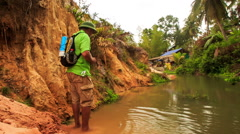 Tourist Walks in Knee-deep River of Fairy-Stream by Rocks Stock Footage