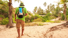 Tourist Goes along Path among Palms in Fairy-Stream Park Stock Footage