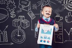 Little boy as a businessman with mustache shows graph of the company's business Stock Photos