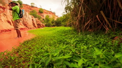 Tourist Photos Rocks of Fairy-Stream by Grass against Plants Stock Footage