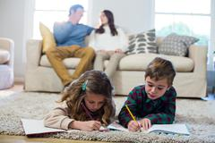 Children doing homework with parents in background Stock Photos