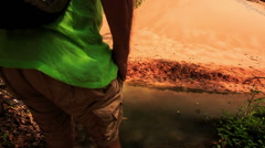 Tourist Barefoot Crosses Stream to Sandy Bank in Park Stock Footage