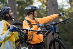 Biker couple carrying mountain bike and pointing in distance Stock Photos