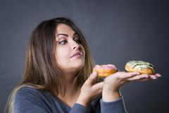 Beautiful young caucasian plus size model posing with donuts on a gr Stock Photos