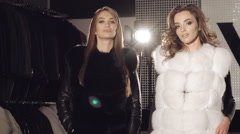 Two models posing in rich fur coats in boutique for advertising. Slowly Stock Footage