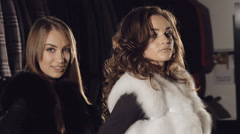 Two enjoyable ladies posing in rich fur coats in boutique. Slowly Stock Footage