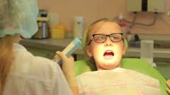 Dentist puts baby dental fillings with blue light Stock Footage
