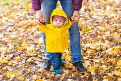 Father and Son walking. Baby taking first steps with father help in autumn Stock Photos