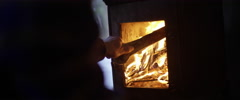 Man putting firewood in wood burning stove Stock Footage