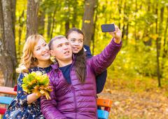 Family, childhood, season, technology and people concept - happy family Stock Photos