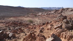 Bedouin caravan walking through stony desert in the Hoggar Mountains Stock Footage