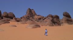 Bedouin walk on red sand in wadi in the Saharan desert on a sunny day Stock Footage