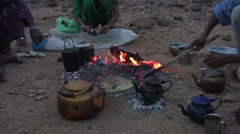 Bedouins making bread in the desert in the open fire and covers it with sand Stock Footage