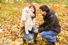 Happy and young family relaxing together in golden and colorful autum nature Stock Photos