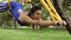 Anti-gravity Yoga, woman doing yoga exercises with hammock in the park Stock Footage