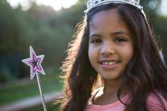Portrait of girl in tiara and wand Stock Photos