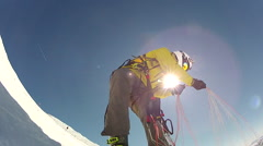 Man untangling parachute as he prepares to go speed riding flying down mountain. Stock Footage
