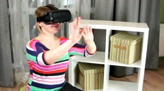 Girl delighted with the images on the screen of virtual reality glasses Stock Footage
