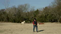 Rancher and horse walking in field Stock Footage