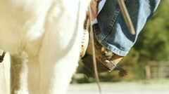 Rancher climbing on horseback Stock Footage