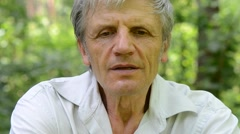 Portrait of gray-haired man with wrinkled, which tells story Stock Footage