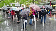 People waiting in line under umbrella's. Stock Footage