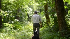 Man with a dog walking on a path in the woods Stock Footage
