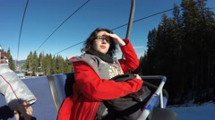 Young girl in a red coat, sitting happily on ski lift chair Stock Footage