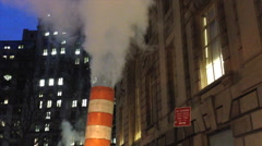 Steam vapor is vented through a red-and-white stack in New York City. The steam Stock Footage