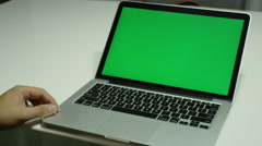 Boy typing on a laptop computer with a green screen Stock Footage