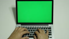 Male typing on a computer with a green screen Stock Footage