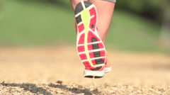 A woman running on a wood chip trail, super slow motion. Stock Footage