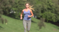 A woman running on a wood chip trail. Stock Footage