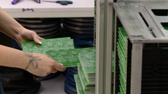 Worker manually sorting circuit boards Stock Footage