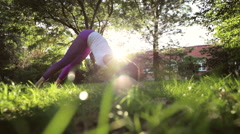 Yoga and pilates exercises on the lawn at sunny morning. Stock Footage